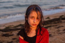 Girl In A Red Towel At The Sea At Sunset. Teenager Girl At The Sea. Rest, Vacation, Childhood.