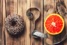 Question Sign Made Of Measuring Tape Between Chocolate Donut And Red Orange On Wooden Surface. Flat Lay