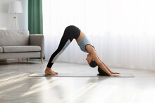Lady Practicing Yoga, Standing In Downward Facing Dog Pose