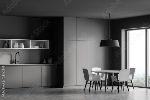 Obraz Grey kitchen interior with dining table and chairs near window, concrete floor - fototapety do salonu