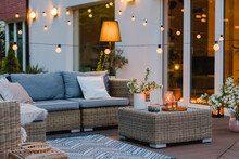 Summer Evening On The Terrace Of Beautiful Suburban House With Patio With Wicker Furniture And Lights