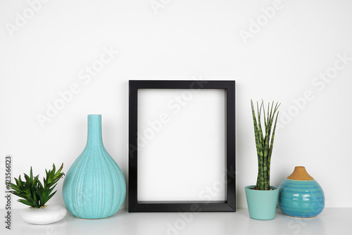 Obraz Mock up black frame with houseplants and blue decor. White shelf against a white wall. Copy space. - fototapety do salonu