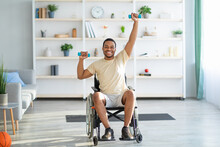 Physical Activities For Disabled People. Handicapped Man In Wheelchair Making Rehabilitation Exerises With Dumbbells