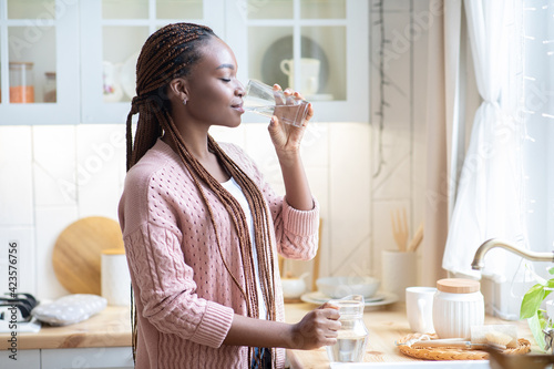 Obraz na plátne Thirsty African American Woman Drinking Water From Glass In Kitchen At Home