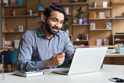 Fototapeta Young bearded indian business man teacher talking, teleworking, having virtual classroom meeting working on laptop computer giving online webinar training, remote class on video conference call. obraz