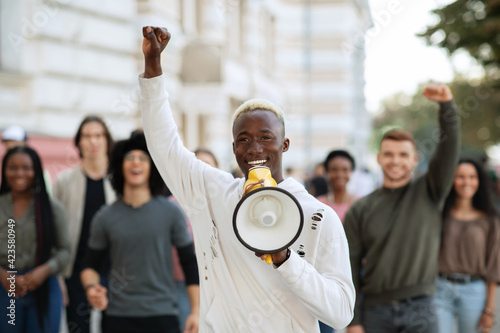 Fototapeta Emotional black guy activist with megaphone on the street