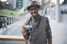 Young Black Man Holding Instant Camera Smiling