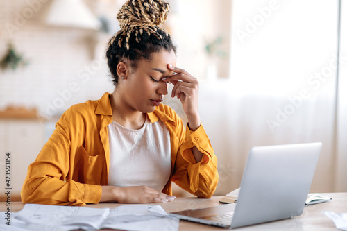 Fototapeta Overworked frustrated young african american student girl or freelancer, in casual clothes, studying or working at home uses laptop, thinking about a problem taking break experiencing stress need rest obraz