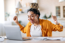 Overjoyed Excited African American Girl With Dreadlocks, Freelancer, Manager Working Remotely At Home Using Laptop, Looks At Screen With Surprise, Smiling Face, Gesturing With Hands, Got A Dream Job