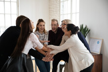 Overjoyed Multiethnic Businesspeople Join Stack Hands In Pile Involved In Teambuilding Activity In Office. Happy Diverse Multiracial Colleagues Coworkers Participate In Team Training At Meeting.