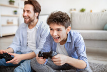 Quarantine Entertainment. Overjoyed Dad And Son Competing For Win On Gamepad At Home, Spending Weekend Together