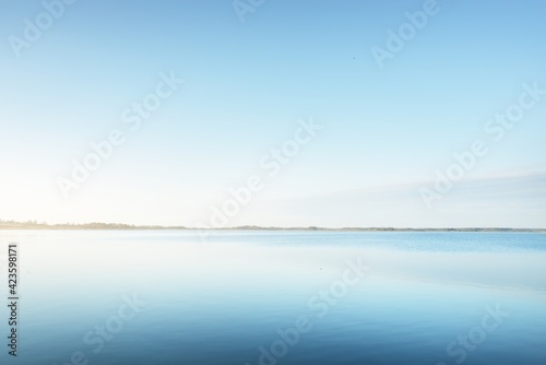 Fototapeta Panoramic aerial view of the blue forest lake (river) at sunset. Soft sunlight, clear sky, reflections on water. Early spring. Idyllic pastoral landscape. Nature, environment, ecology, ecotourism obraz