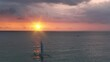 Sunrise over sailboat cruising at ocean slow motion aerial. Nature seascape. People on sailing boat. Water transportation. Summer voyage at sun open sea. Pink sky with purple clouds. Marine holiday