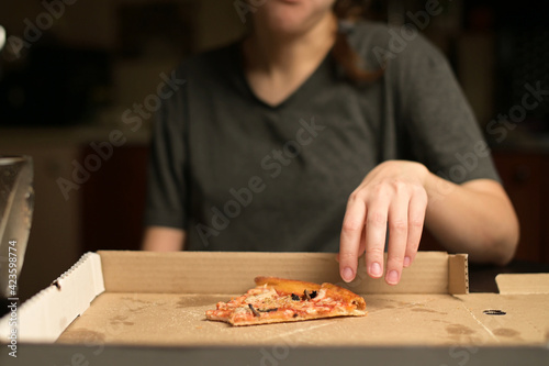 Fototapeta Woman takes a bite of the pizza and puts it in the box
