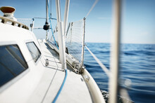 White Yacht Sailing In The North Sea After The Storm. Norway. Close-up Of Boat Side Railing. Clear Blue Sky, Soft Sunlight. Transportation, Cruise, Recreation, Regatta, Sport, Leisure Activity
