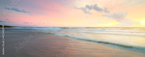 Obraz Baltic sea at sunset. Dramatic sky, blue and pink glowing clouds, soft golden sunlight. Waves, splashing water. Picturesque dreamlike seascape, cloudscape, nature. Panoramic view, long exposure - fototapety do salonu