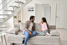 Happy Young Indian Father With Teenage Child Daughter Having Fun Enjoying Talking Spending Time At Home. Smiling Dad And Teen Kid Girl Having Conversation Sitting On Sofa In Modern House Living Room.