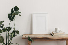 White Portrait Frame Mockups On Vintage Bench, Table. Cup Of Coffee On Pile Of Books And Monstera Potted Plant. White Wall Background. Scandinavian Interior, Neutral Color Palette. Artistic Display.