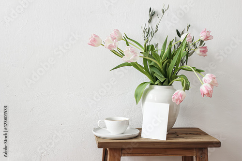 Fototapeta Rustic Easter still life scene. Blank greeting card mockup, cup of coffee and floral bouquet in white ceramic vase on wooden bench. Spring photo. Pink tulips flowers, olive tree branches on table. obraz