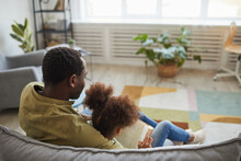 Back View At Loving African-American Father And Daughter Sitting On Couch Together In Cozy Home Interior, Copy Space