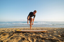 Surfer Fastens Leash At Leg, Going To Surf In Ocean At Morning Time. Tropical Environment.