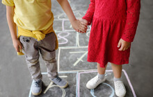 Little Boy And Girl On Background Hopscotch Which Drawn On Asphalt. Children Playing Hop Scotch Game On Playground Outdoors On A Sunny Day. Kids Having Fun. Best Friends