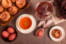 Easter Breakfast. Still Life With Colored Eggs, Tea With Lemon In A White Cup, Muffins. On The Table Is A Glass Vase With Sweet, Strawberry Jam And A Bouquet Of Flowers. Gray Wooden Background.