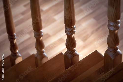 Tela Element of a wooden interior staircase. Wooden baluster close-up.