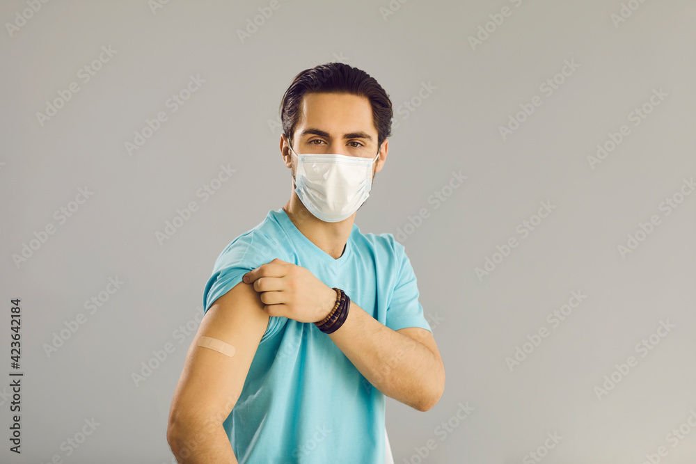 Fototapeta Vaccination of the population. Close up on gray background man in medical mask shows hand with patch at vaccine injection site. Young man received a vaccine against the corona virus.