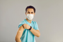 Vaccination Of The Population. Close Up On Gray Background Man In Medical Mask Shows Hand With Patch At Vaccine Injection Site. Young Man Received A Vaccine Against The Corona Virus.