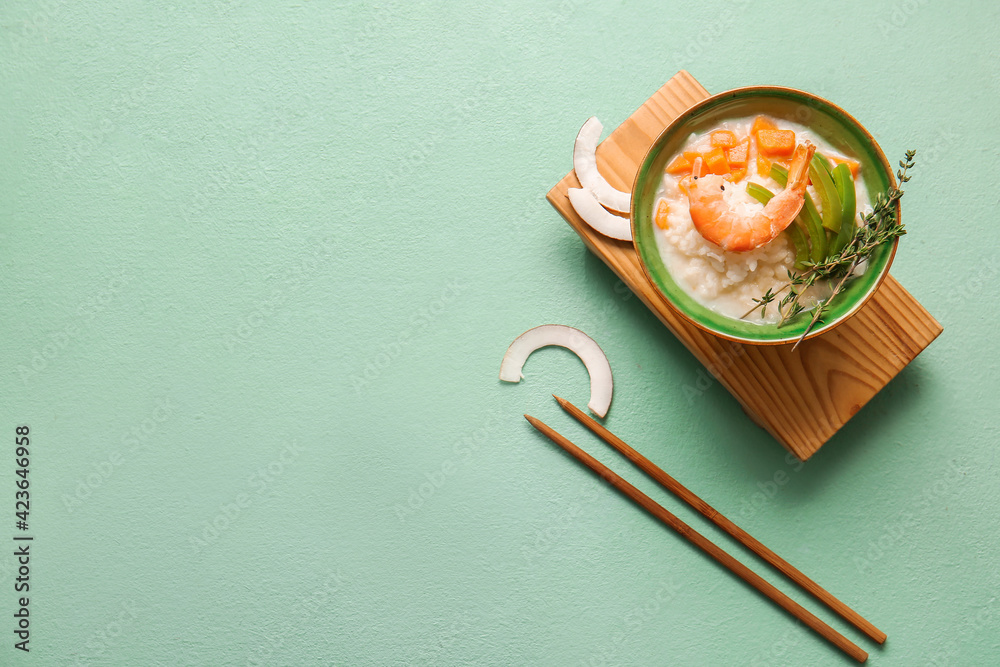 Fototapeta Bowl with Thai rice soup on color background