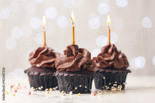 Fotografie, Obraz Tasty chocolate cupcakes with candles on blurred background