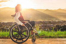Disabled Handicapped Woman Sitting On Wheelchair Sunset Background. International Disability Day.