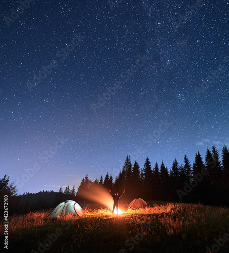 Fotografie, Obraz Male traveler standing near campfire and pointing at stars.