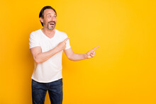 Photo Of Funny Bearded Man Indicate Forefingers Look Empty Space Wear White T-shirt Isolated Yellow Background