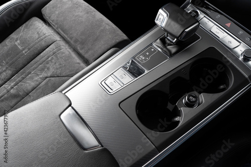 Black luxury modern car Interior. Steering wheel, shift lever and dashboard. Detail of modern car interior. Automatic gear stick. Part of leather seats with stitching in expensive car