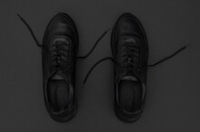 Flat Lay Black Classic Leather Men's Sneakers On Black Background. Fashionable Youth Sports Sneakers. Sports Casual Shoes Top View Copy Space. Footwear For Fitness, Running, Healthy Lifestyle