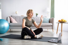 Mature Woman In Sports Clothes Sitting On Yoga Mat In Front Of Laptop, Ready For Domestic Workout, Greeting Her Trainer