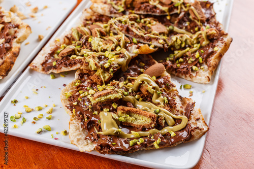 Fotografia, Obraz Bruschetta dolce fatta di pasta per la pizza con nutella, biscotti al pistacchio