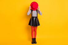 Full Length Photo Of Funny Childish Young Girl Dressed Leather Skirt Hiding Red Headwear Isolated Yellow Color Background