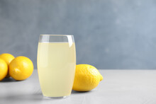 Glass Of Lemonade And Fresh Fruits On Light Table. Space For Text