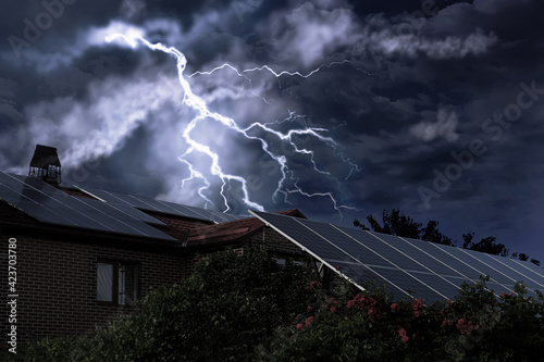 Obraz Dark cloudy sky with lightning over house. Stormy weather - fototapety do salonu