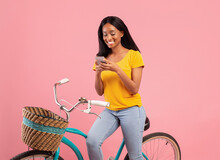 Lovely Black Woman With Vintage Bicycle Using Smartphone Over Pink Studio Background