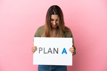 Young Caucasian Woman Isolated On Pink Background Holding A Placard With The Message PLAN A