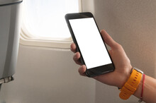Mockup Image Of Woman's Hands Holding A Black Smart Phone With Blank Desktop Screen Next In The Cabin At The Window Airplane