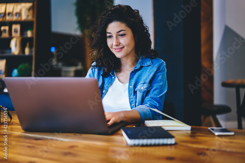Skilled hipster girl reading text publication and browsing media content during social networking via netbook app, Caucaisan female freelancer doing distance job on modern netbook connecting to 4g