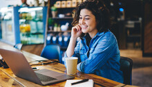 Happy Caucaisan Woman 20s Watching Positive Movie Video During Leisure In Coffee Shop, Cheerful Hipster Girl Smiling While Reading Received Email Message Or Funny Publication In Social Media