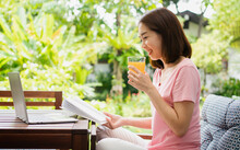 Mid-age Asian Woman Reading A Book And Hold Orange Juice Glass In The Home. Concept Of  Health Care And Eating For Healthy