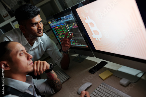 Papel de parede Pensive traders discussing ascending bitcoin price chart on computer screen when