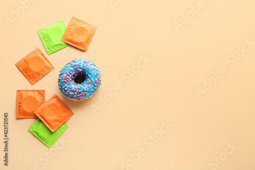 Fototapeta Sweet donut and condoms on color background. Erotic concept obraz na płótnie